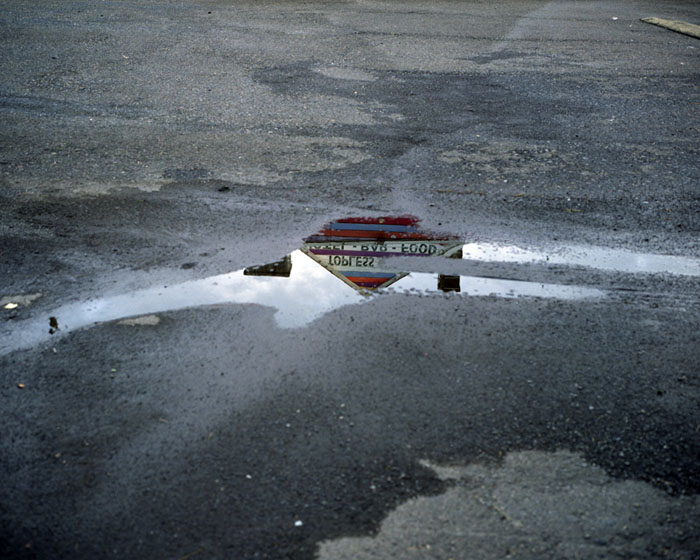 Topless bar reflected in puddle, Doylestown, Penna. 2010